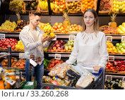 Купить «Portrait of woman satisfied with purchases in shopping cart at fruit store», фото № 33260268, снято 7 ноября 2019 г. (c) Яков Филимонов / Фотобанк Лори