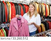 Купить «Smiling female customer satisfied with purchases in leather clothing boutique», фото № 33260512, снято 5 сентября 2018 г. (c) Яков Филимонов / Фотобанк Лори