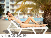 Купить «A beautiful woman with a perfect slim figure in a white bikini swimsuit is relaxing on sunbed by pool», фото № 33262164, снято 9 сентября 2017 г. (c) katalinks / Фотобанк Лори