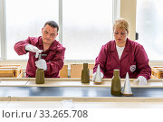 Sopot, Bulgaria - May 17, 2016: Workers are tightening explosive elements of anti-tank rocket-propelled grenades (RPG, bazooka) at an assembly line in a munition factory. Working with white gloves. Стоковое фото, фотограф Zoonar.com/Cylonphoto / age Fotostock / Фотобанк Лори