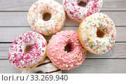 Купить «close up of glazed donuts on grey boards», фото № 33269940, снято 6 июля 2018 г. (c) Syda Productions / Фотобанк Лори