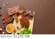 Купить «chocolate with hazelnuts, cocoa beans and powder», фото № 33270108, снято 1 февраля 2019 г. (c) Syda Productions / Фотобанк Лори
