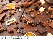 Купить «cocoa beans, chocolate, nuts and cinnamon sticks», фото № 33270116, снято 1 февраля 2019 г. (c) Syda Productions / Фотобанк Лори
