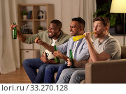 Купить «friends or soccer fans with ball and beer at home», фото № 33270128, снято 28 декабря 2019 г. (c) Syda Productions / Фотобанк Лори