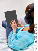 Купить «woman with tablet pc and headphones at home», фото № 33270376, снято 20 декабря 2013 г. (c) Syda Productions / Фотобанк Лори