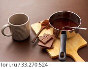 Купить «pot with hot chocolate, mug and cocoa powder», фото № 33270524, снято 1 февраля 2019 г. (c) Syda Productions / Фотобанк Лори