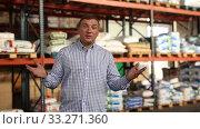 Купить «Male buyer talking about fertilizer in hardware store», видеоролик № 33271360, снято 9 октября 2019 г. (c) Яков Филимонов / Фотобанк Лори