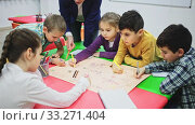Купить «Teacher and collective of elementary age children draw together a board game», видеоролик № 33271404, снято 31 марта 2020 г. (c) Яков Филимонов / Фотобанк Лори
