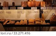 Купить «Variety of freshly baked bread, baguettes and buns on shelves in bakery shop. Price tags in Catalan with names of bakery products», видеоролик № 33271416, снято 5 февраля 2020 г. (c) Яков Филимонов / Фотобанк Лори