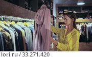 Portrait happy woman choosing new clothes on hangers in shop. Стоковое видео, видеограф Яков Филимонов / Фотобанк Лори