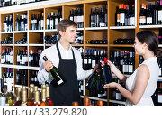 Купить «portrait of male seller showing bottle of wine to female customer in wine shop», фото № 33279820, снято 6 июня 2020 г. (c) Яков Филимонов / Фотобанк Лори