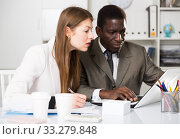 Купить «Young woman and man colleagues working with laptop and papers», фото № 33279848, снято 31 марта 2020 г. (c) Яков Филимонов / Фотобанк Лори