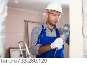 Professional constructor in helmet is sawing wall with circular saw. Стоковое фото, фотограф Яков Филимонов / Фотобанк Лори