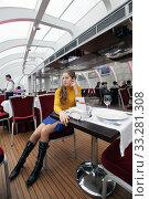 Девушка в яркой одежде в кафе со стеклянным потолком (2011 год). Редакционное фото, фотограф Elizaveta Kharicheva / Фотобанк Лори