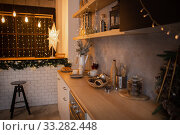 New Years kitchen interior, Christmas wreath hanging on the kitchen wall. New Years decor of kitchen. Стоковое фото, фотограф Екатерина Кузнецова / Фотобанк Лори