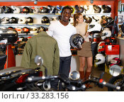 Portrait of young Afro man satisfied with new riding gear at motorcycle shop. Стоковое фото, фотограф Яков Филимонов / Фотобанк Лори