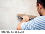 Купить «The process of filling walls. Repair of the living quarters. Interior decoration with putty. Stucco white primer», фото № 33284288, снято 6 июня 2020 г. (c) Екатерина Кузнецова / Фотобанк Лори
