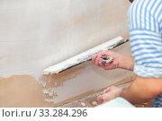 Купить «Worker puts putty on a spatula for plastering internal walls in a living room», фото № 33284296, снято 6 июня 2020 г. (c) Екатерина Кузнецова / Фотобанк Лори