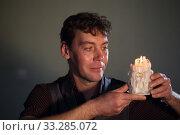 Купить «Молодой человек держит свечу», фото № 33285072, снято 15 февраля 2020 г. (c) Марина Володько / Фотобанк Лори