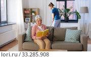 Купить «old woman reading book and housekeeper at home», видеоролик № 33285908, снято 19 января 2020 г. (c) Syda Productions / Фотобанк Лори