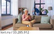 Купить «old woman with smartphone and housekeeper at home», видеоролик № 33285912, снято 19 января 2020 г. (c) Syda Productions / Фотобанк Лори