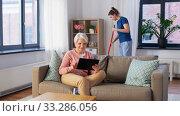Купить «old woman with tablet pc and housekeeper at home», видеоролик № 33286056, снято 19 января 2020 г. (c) Syda Productions / Фотобанк Лори