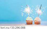 Two cupcakes decorated with sparklers, copy space. Стоковое фото, фотограф Ольга Сергеева / Фотобанк Лори