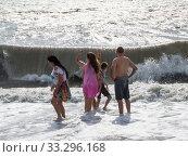Купить «Отдыхающие на линии прибоя смотрят на набегающую волну», фото № 33296168, снято 4 августа 2019 г. (c) Вячеслав Палес / Фотобанк Лори