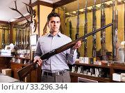 Nice male hunter choosing shotgun in store. Стоковое фото, фотограф Яков Филимонов / Фотобанк Лори