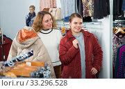 Купить «Women trying coat in clothing boutique», фото № 33296528, снято 6 декабря 2018 г. (c) Яков Филимонов / Фотобанк Лори