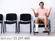 Купить «Young injured man waiting for his turn in hospital hall», фото № 33297408, снято 3 мая 2019 г. (c) Elnur / Фотобанк Лори