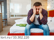 Купить «Drunken man awake in bed with bottle of wine», фото № 33302220, снято 24 ноября 2019 г. (c) Tryapitsyn Sergiy / Фотобанк Лори