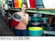 Купить «Young woman customer holding big colored plastic pot for garden», фото № 33302596, снято 6 апреля 2020 г. (c) Яков Филимонов / Фотобанк Лори