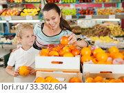 Купить «mother with little boy buying oranges at store», фото № 33302604, снято 20 апреля 2019 г. (c) Яков Филимонов / Фотобанк Лори