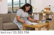 Купить «woman with papers and calculator at home», видеоролик № 33303156, снято 24 февраля 2020 г. (c) Syda Productions / Фотобанк Лори