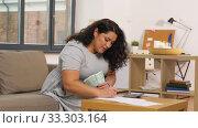 Купить «woman with money, papers and calculator at home», видеоролик № 33303164, снято 24 февраля 2020 г. (c) Syda Productions / Фотобанк Лори