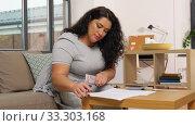 Купить «woman with money, papers and calculator at home», видеоролик № 33303168, снято 24 февраля 2020 г. (c) Syda Productions / Фотобанк Лори