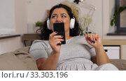 Купить «woman in headphones listens to music on smartphone», видеоролик № 33303196, снято 24 февраля 2020 г. (c) Syda Productions / Фотобанк Лори