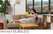 Купить «happy young woman reading book on sofa at home», видеоролик № 33303212, снято 24 февраля 2020 г. (c) Syda Productions / Фотобанк Лори
