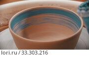 Купить «Pottery - man is painting a clay bowl inside with blue brush on a pottery wheel», видеоролик № 33303216, снято 5 апреля 2020 г. (c) Константин Шишкин / Фотобанк Лори