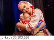A little girl and an adult woman in Russian national dress posing during photoshoot on stage. Mother and daughter together. Стоковое фото, фотограф Кривошеина Елена Леонидовна / Фотобанк Лори