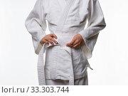 Купить «Stages of correct tying of the belt by a teenager on a sports kimono, step five», фото № 33303744, снято 21 февраля 2020 г. (c) Иванов Алексей / Фотобанк Лори
