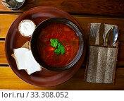 Купить «Ukrainian borscht red-beet soup on bowl, served with bread and salo», фото № 33308052, снято 4 апреля 2020 г. (c) Яков Филимонов / Фотобанк Лори