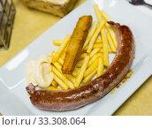 Купить «Tasty rustic sausage with french fries served at plate with white sauce», фото № 33308064, снято 4 апреля 2020 г. (c) Яков Филимонов / Фотобанк Лори