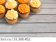 cupcakes with frosting on wooden boards background. Стоковое фото, фотограф Syda Productions / Фотобанк Лори