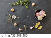 Купить «garlic in bowl and rosemary on stone surface», фото № 33308580, снято 6 сентября 2018 г. (c) Syda Productions / Фотобанк Лори