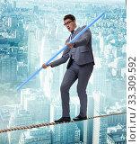 Купить «Businessman doing tightrope walking in risk concept», фото № 33309592, снято 6 сентября 2010 г. (c) Elnur / Фотобанк Лори