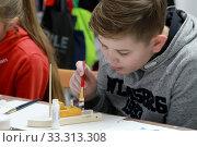 Купить «Мальчик окрашивает корпус деревянного кораблика. Детский мастер-класс в студии», фото № 33313308, снято 26 января 2020 г. (c) Ирина Борсученко / Фотобанк Лори