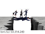 Купить «Businessman acting as a bridge in support concept», фото № 33314240, снято 3 апреля 2020 г. (c) Elnur / Фотобанк Лори