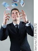 Купить «Young man in formalwear throwing money.», фото № 33314572, снято 31 марта 2020 г. (c) PantherMedia / Фотобанк Лори